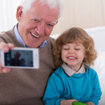 Smiling grandfather with grandson taking photo by mobile phone